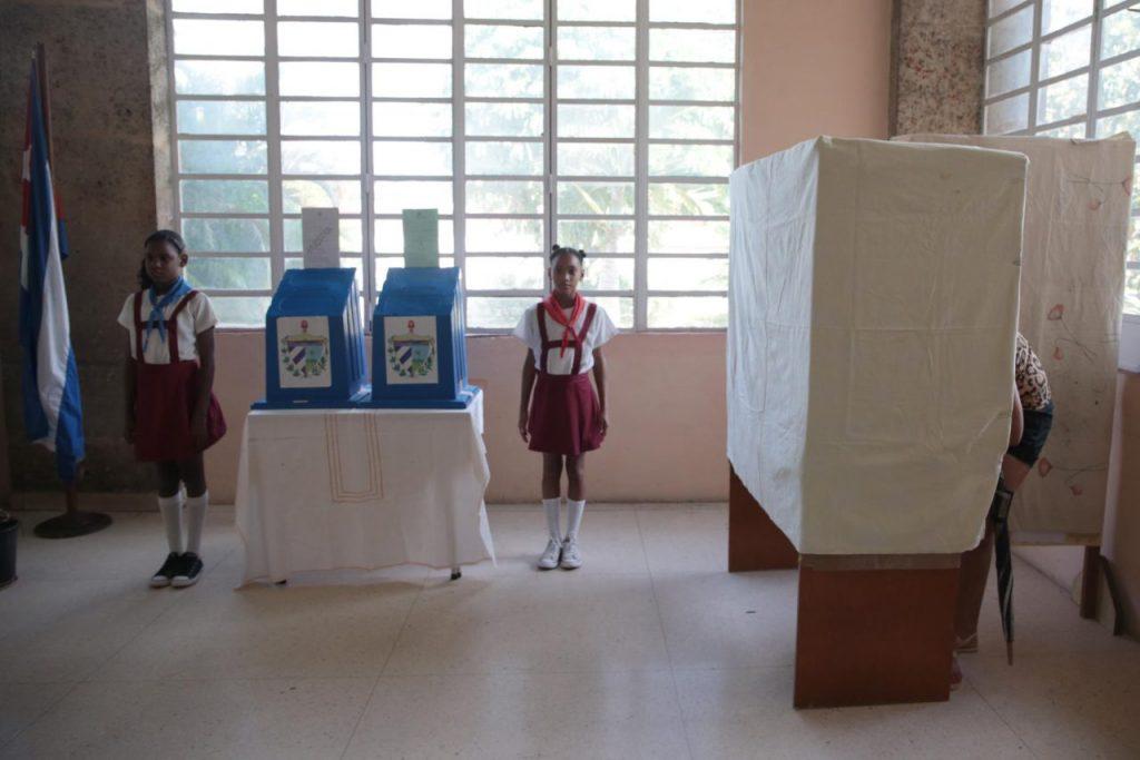 """Пионерчета охраняват изборните урни, докато избирател гласува в """"тъмната стаичка"""". Снимка: Resumen Latinoamericano"""