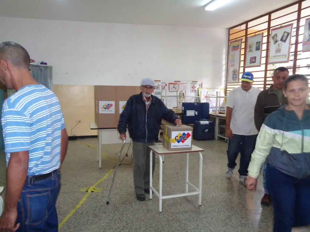 След като гласува машинно зад импровизирания параван от разгърнати кашони върху маса (в дъното), избирателят пуска и хартиения фиш, издаден му от машината, в урна в средата на класната стая. Снимка: Къдринка Къдринова