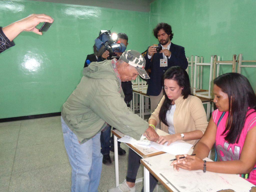 Евродепутатът Жоао Пимента (с фотоапарата в дъното) снима как избирател дава пръстов отпечатък, след като вече е гласувал. Снимка: Къдринка Къдринова