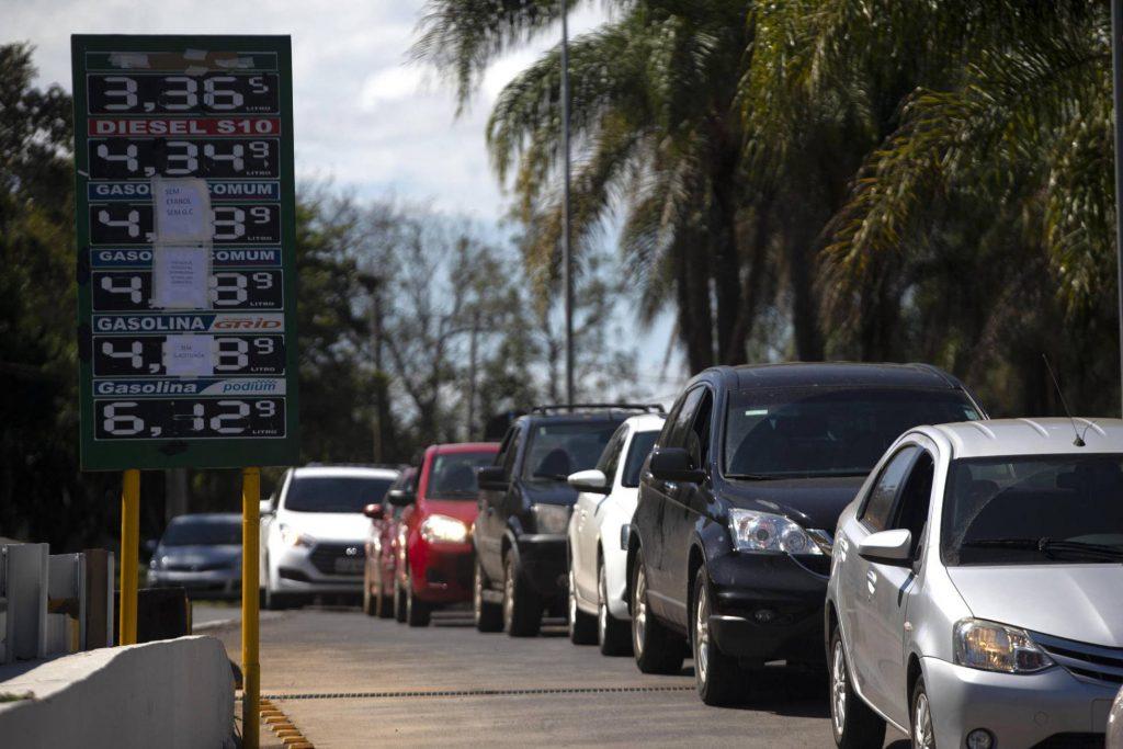 Опашка от коли край бензиностанция, която е обявила, че затваря заради липса на зареждане. На таблото личат цените на горивата в реали. Снимка: EFE