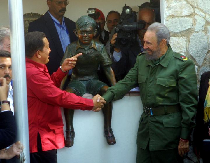 Уго Чавес и Фидел Кастро си стискат ръцете пред бронзовата фигура на малкия Ернесто в къщата музей в Алта Грасия по време на посещението им там през 2006 г. Снимка: cubadebate