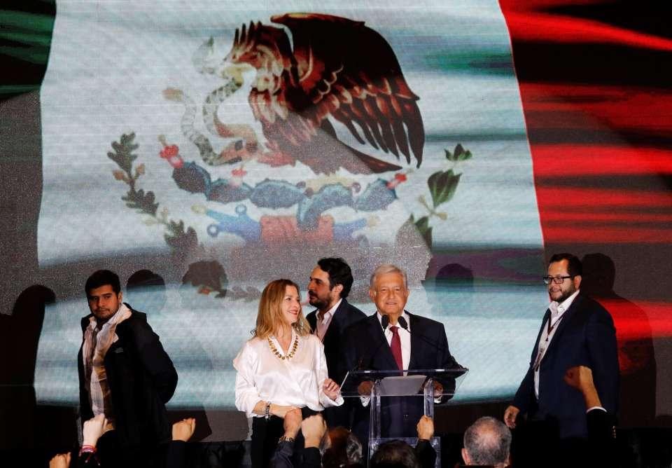 На митинга в столицата Мексико след победата на Обрадор до него застана и жена му–филоложката и активистка на неговата партия Беатрис Гутиерес Мюлер. А зад тях се подредиха и тримата му пораснали сина от първия му брак, също видни дейци на Morena. Снимка: El Pais