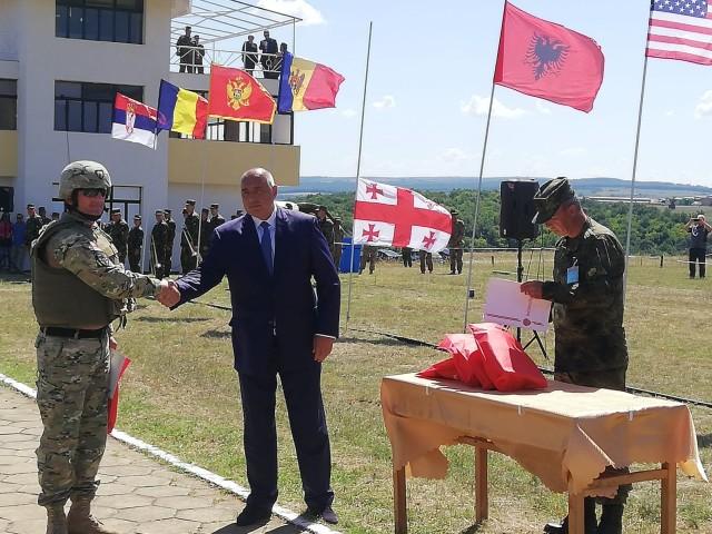 Премиерът Борисов поздравява бойците от ученията в Ново село на фона на знамената на страните участнички. Снимка: Фейсбук