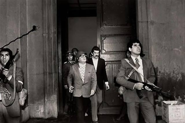 """Президентът на Чили Салвадор Алиенде (в средата, с каската) сред защитниците на двореца """"Ла Монеда"""" в последните часове на живота си. Снимка: Пренса Латина"""