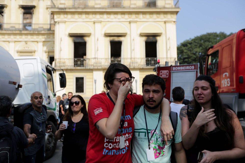 Хората оплакват унищоженото от жестокия пожар в Националния музей на Бразилия край обгорената му сграда, докато пожарникарите се опитват да охладят стените на сградата, за да не рухнат и те. Снимка: EFE