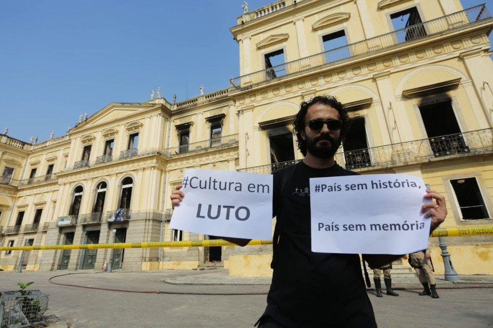 """Този мъж, застанал пред обгорялата музейна сграда, през чиито празни прозорци вече прозира само небето, държи надписи: """"Културата е в траур"""" и """"Страна без история, страна без памет"""". Снимка: EFE"""