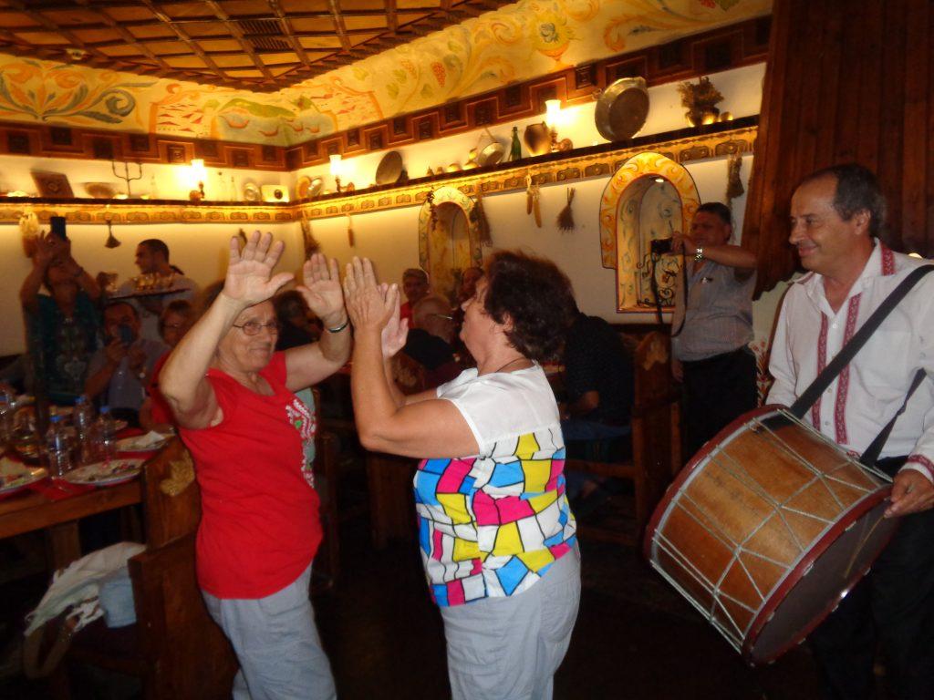 Българката Теодора Пиперкова (с червената блуза), която преди 46 г. е последвала мъжа си в Коста Рика, танцува ръценица заедно със сестра си в механата, в която латиногрупата бе посрещната с българска народна музика. Снимка: Къдринка Къдринова