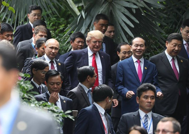 """Путин и Тръмп разговарят """"на крак"""", до тях сияе усмихнат виетнамският президент Чан Дай Куанг, а от другата му страна е китайскиет лидер Си Дзинпин. Снимка: РИА"""