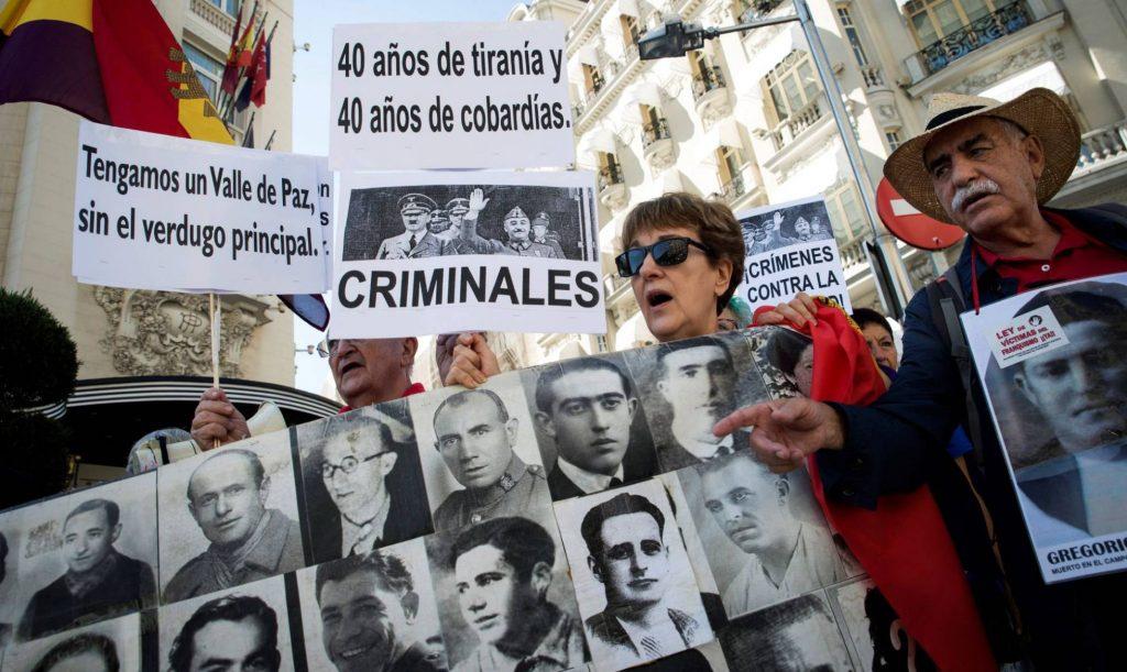 """Семейства на репресирани от франкизма демонстрираха днес пред сградата на парламента в Мадрид. На един от плакатите пише: """"Нека получим Долина на мира, без главния палач"""". Снимка: EFE"""