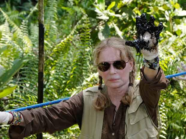 """Миа Фароу в амазонската джунгла с черни от петролни замърсявания ръке–по време на кампанията, с която Еквадор претендираше за компенсации от """"Шеврон"""". Снимка: Gobierno de Ecuador"""