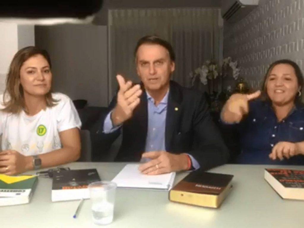 В нощта след победата си Болсонаро се обърна към бразилците по любимия си начин–през Фейсбук. До него беше младата му жена Мишел (в бяло) и интерпретаторка за хора с увреден слух, а на масата личаха Библията и конституцията, която новоизбраният президент се зарече да спазва. Снимка: Фейсбук