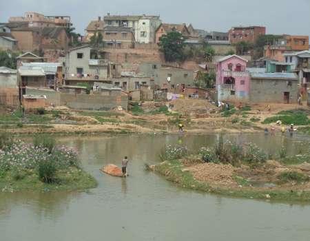 Мъж пренася на кануто си тухли по един от каналите в Антананариво. Снимка: Къдринка Къдринова
