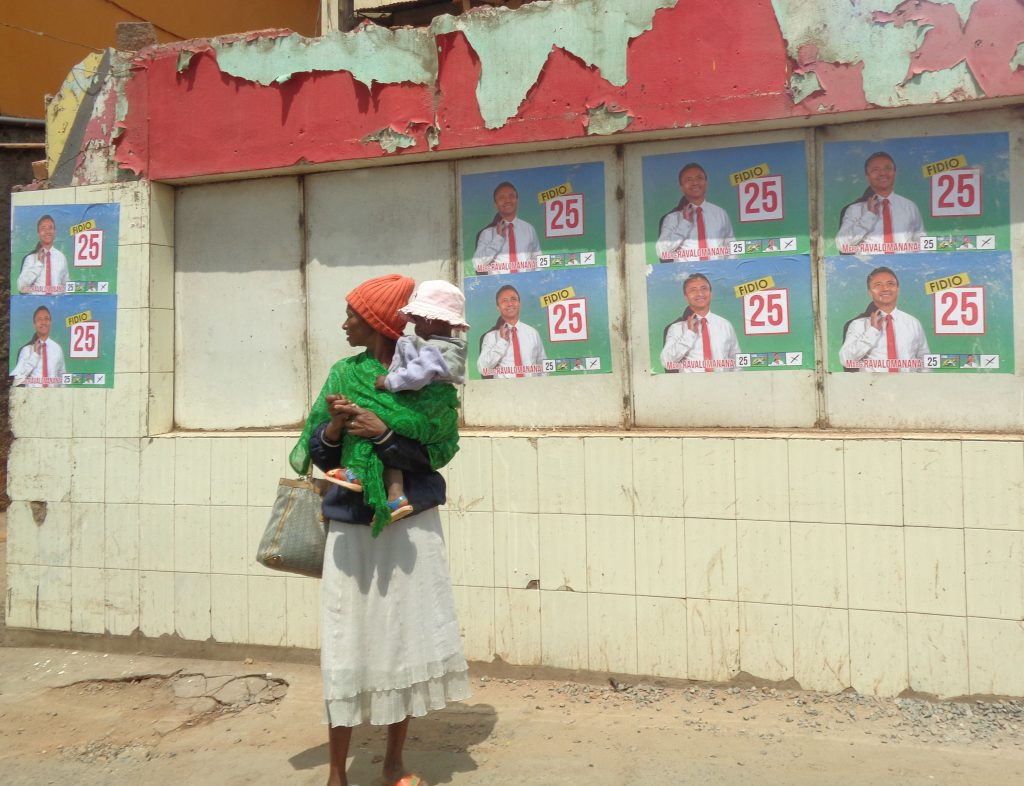 Бедна жителка на Антананариво заеднос детето си край предизборни плакати с Марк Раваломанана. Снимка: Къдринка Къдринова