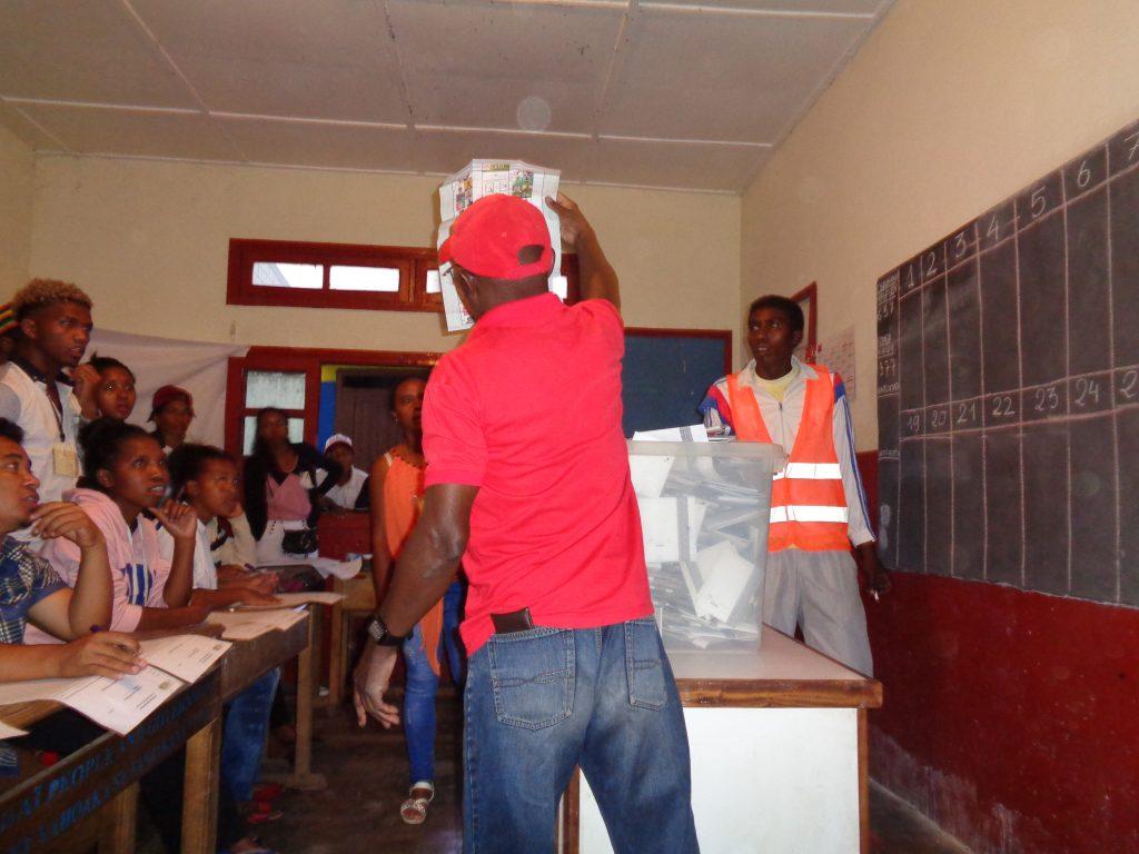 Член на изборната комисия показва всяка бюлетина на всички страни в стаята, а друг отбелязва гласа на дъската. Снимка: Къдринка Къдринова