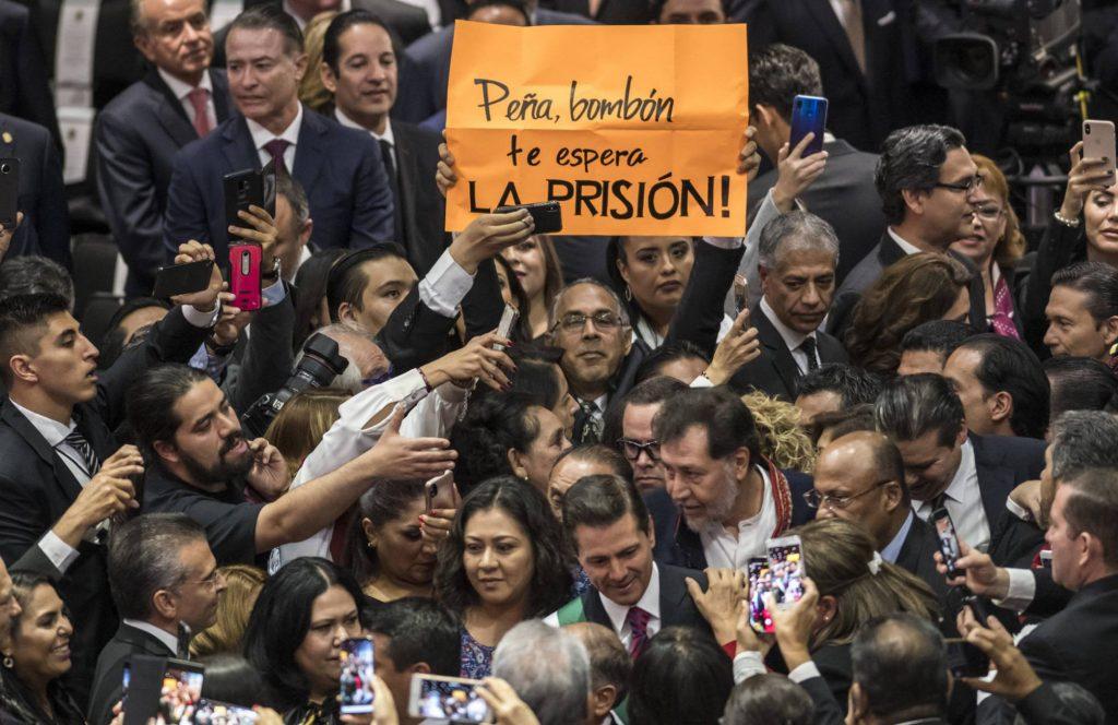 """При влизането на досегашня президента Енрике Пеня Нието (в центъра на долната част на снимката) опозиционен депутат размаха плакат, на който пишеше: """"Пеня, бонбоне, чака те затвор!"""". Снимка: El Pais"""