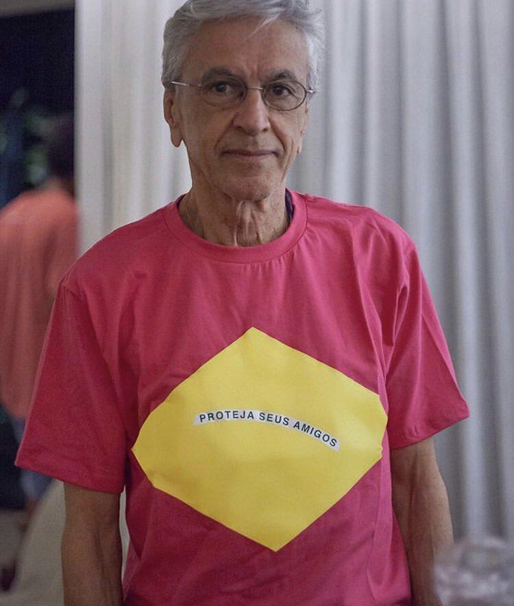 """Певецът, композиторът и китарист Каетано Велозо се снима в розова тениска напук на министърката Дамареш Алвеш. На жълтия ромб, наподобяващ онзи от националния флаг, пише: """"Защити приятелите си"""". Снимка: Туитър"""