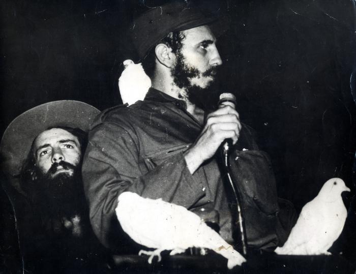 Фидел Кастро, накацан от бели гълъби, говори пред множеството на 8 януари 1959 г. До него е Камило Сиенфуегост. Снимка: Cubadebate