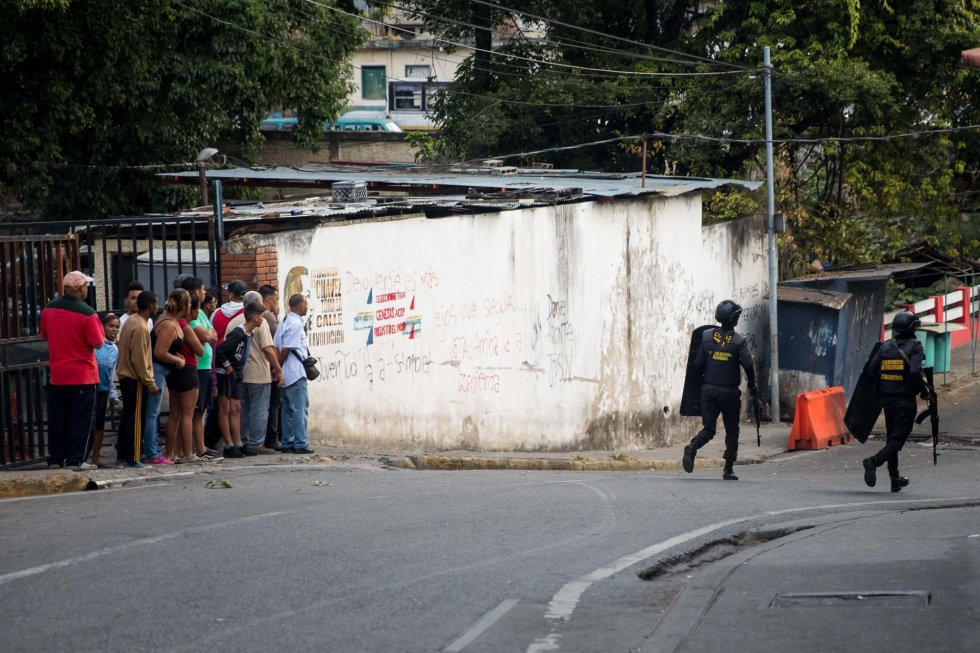Жители на един от кварталите на Каракас притеснено гледат след бойци от спецчастите, които проверяват района за въоръжени лица. Снимка: El Pais