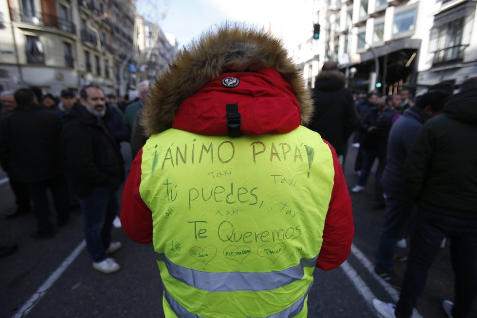 """""""Кураж, татко! Ти можеш!"""" -е написало детето на този стачкуващ шофьор на такси върху жълтата м жилетка. Снимка: El Pais"""
