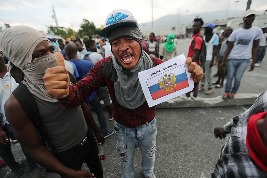 Демонстрант в Порт-о-Пренс показва пред камерите принтирано изображение на руския национален флаг. Снимка: Resumen Latinoamericano