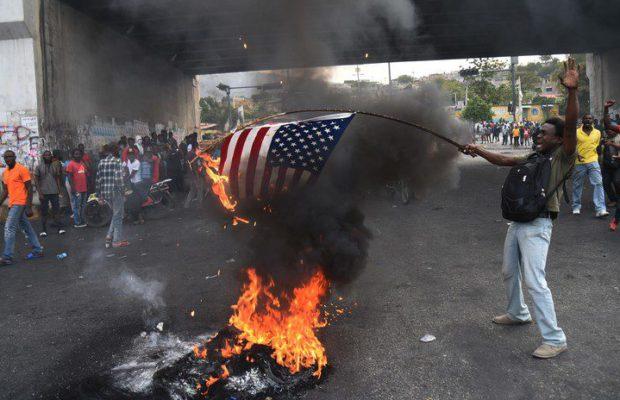 Американското знаме пламна по време на демонстрация в Порт-о-Пренс. Снимка: Resumen Latinoamericano