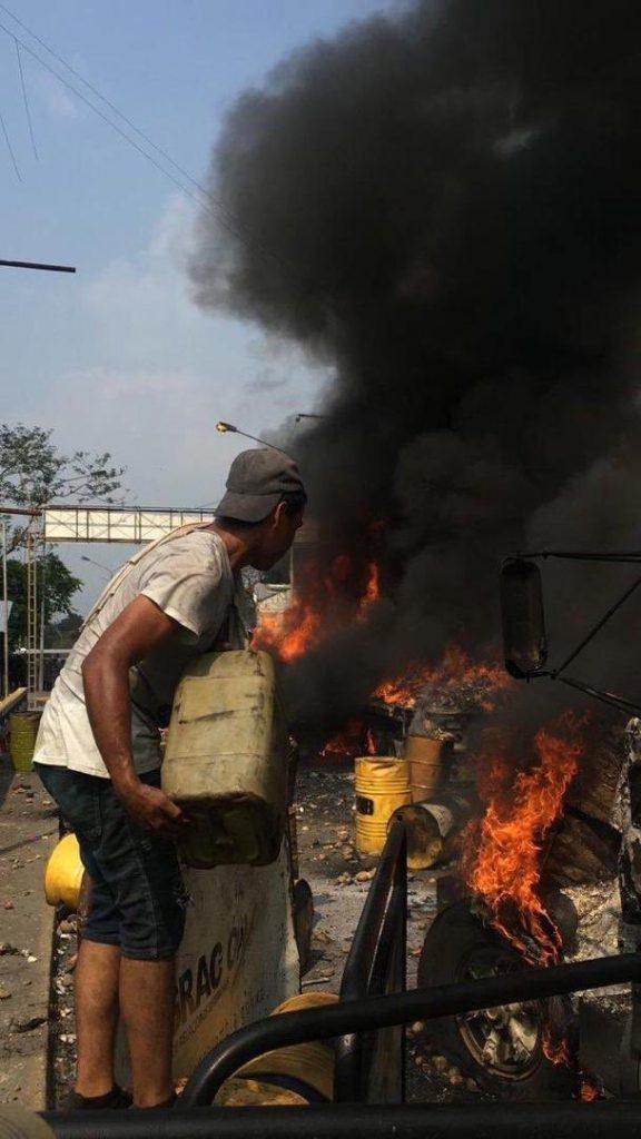 Популярна в социалните мрежи стана снимката на този демонстрант, подливащ бензин от бидон в огъня на горящия камион. Снимка: Фейсбук