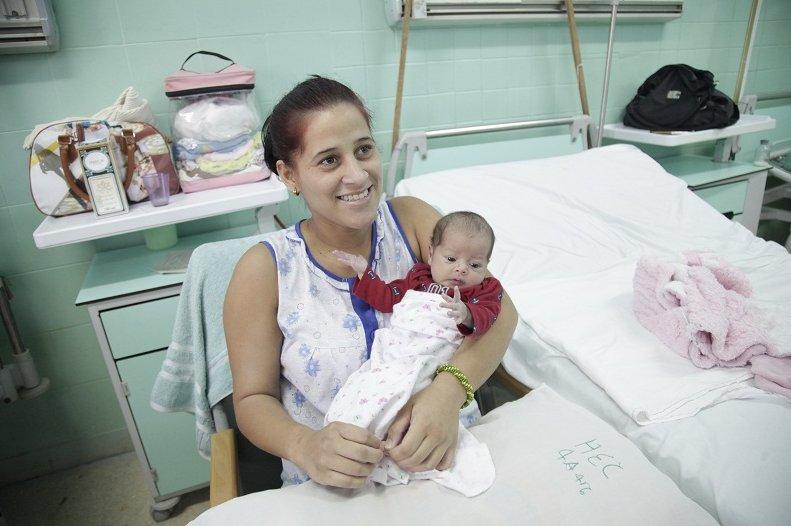 22-годишната Дариен Ернандес вече знае, че семейният ѝ дом е разрушен, но въпреки това е щастлива, защото дъщеричката ѝ Кевелин е невредима, макар родилният дом да е бил помлят от торнадото. Снимка: Juventud Rebelde