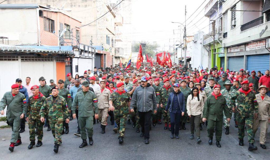 Венесуелският президент Николас Мадуро (в средата, в сиво яке) заедно с други ръководни държавни и военни дейци крачи заедно с представители на въоръжените сили и на народните милиции по улица в град Маракай. Снимка: EFE
