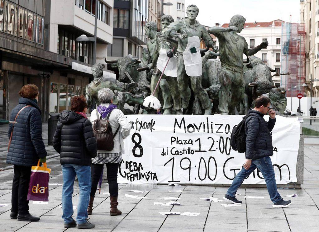 """В Памплона мъжките фигури от паметника, увековечил традиционното за града надбягване с бикове, бяха """"украсени"""" с домакински престилки и с уреди за чистене в чест на 8 март, а отпред бе опънат плакат, известяващ за началния час за феминисткото шествие. Снимка: EFE"""