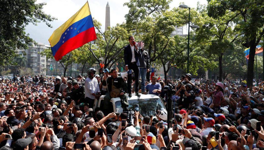 Хуан Гуайдо говори пред привърженици в Каракас. Зад него на покрива на колата е Леополдо Лопес. Снимка: El Pais