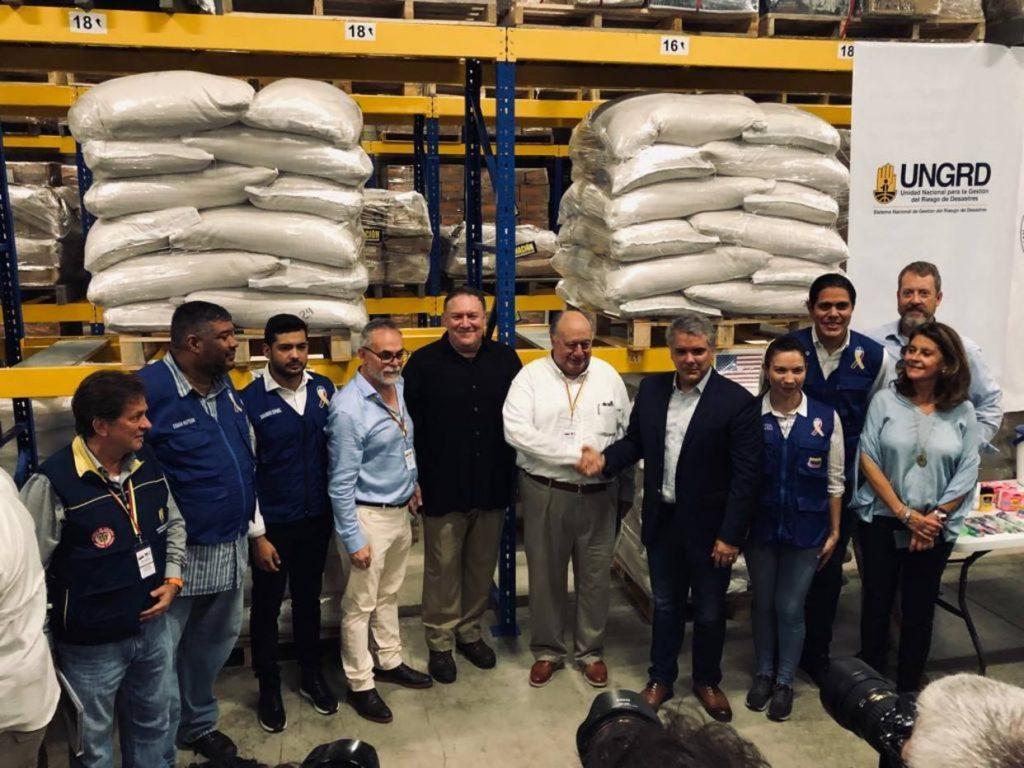 Майк Помпео (в центъра) се снима заедно с придружаващите го лица в склад в колумбийския град Кукута, където още се пазят така и не влезлите във Венесуела американски пратки от февруари. Снимка: atoodomomento.com
