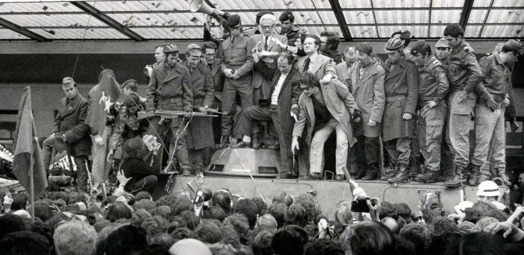 Алваро Кунял държи реч на гарата в Лисабон непосредствено след завръщането си от емиграция на 27 април 1974 г., покачен върху корпуса на танк. До него е Марио Соариш. Заобикалят ги бойци от Движението на капитаните. Снимка: geral forum