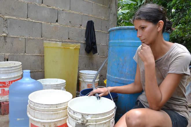 Млада венесуелка чака да се напълни кофата ѝ от капещ маркуч на един от пунктовете за зареждане с вода в Каракас. Заради саботажите срещу електросистемата на страната спряха водните помпи и това е най-тежкият удар по населението. Снимка: Punto de Corte