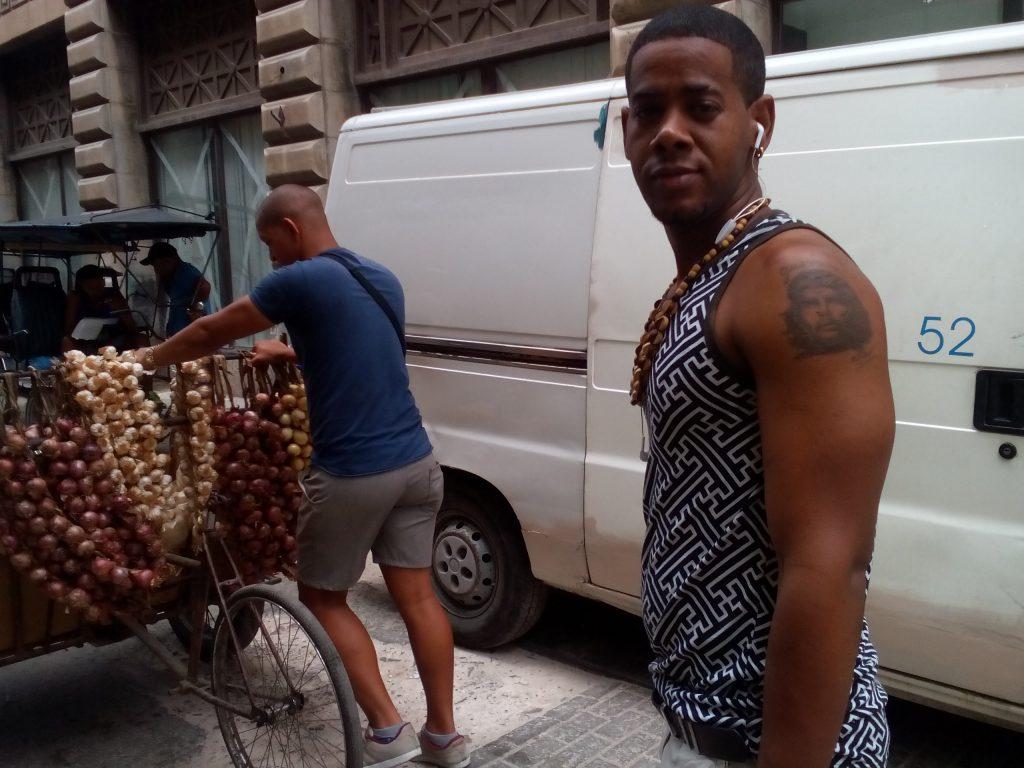 Този млад продавач на лук изостана от приятеля си,тикащ количката, за да покаже домре пред обектива бицепса си татуирания портрет на Че. Снимка: Къдринка Къдринова
