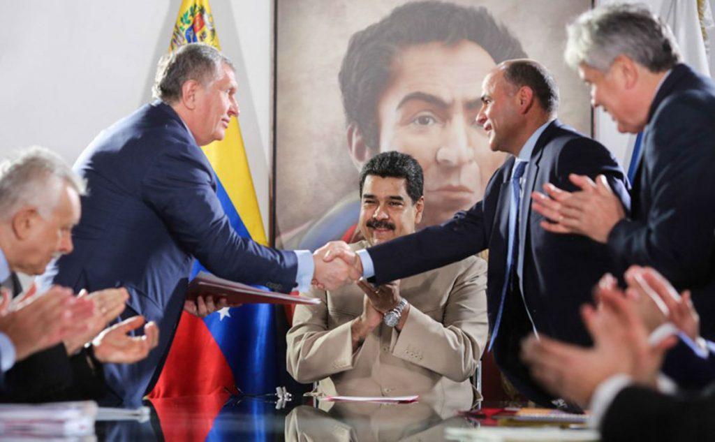 """Шефът на """"Роснефт"""" Игор Сечин и венесуелският министър на петрола Мануел Кеведо си стискат ръцете пред очите на президента Николас Мадуро след сключено споразумение през 2017 г. за съвместна разработка на нефтени находища. Снимка: Twitter"""