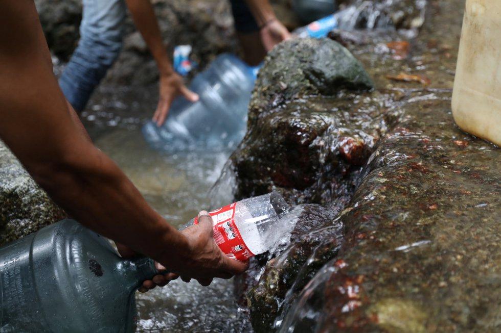 Хора наливат вода от поточе на планината Уарайра Репано. Снимка: EFE