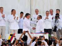 Президентът на Колумбия Мануел Сантос стиска ръката на представителя на ФАРК Родриго Лондоньо-Тимошенко на церемонията в Картахена де Индиас под аплодисментите на високопоставени гости от света