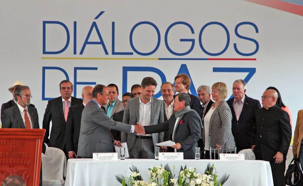 Стартът на преговорите. Ръкуват се Хуан Камило Рестрепо (вляво) от името на колумбийското правителство и Пабло Белтран от името на ELN. Между тях е външният министър на Еквадор Гийом Лон. Снимка: resumenlatinoamericano.org