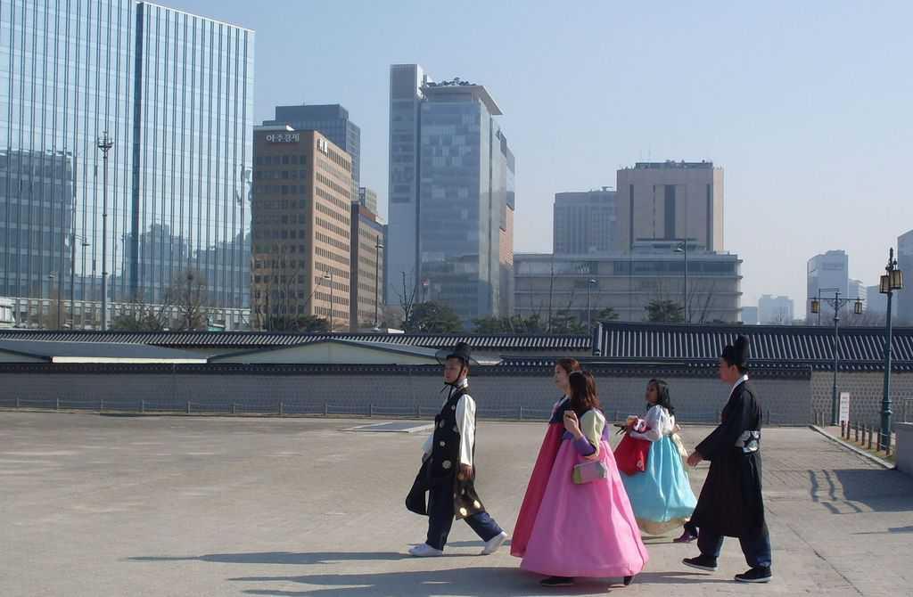 Южнокорейци в носии ханбок излизат от двореца Кьонбокун на фона на модерен Сеул. Снимка: Къдринка Къдринова