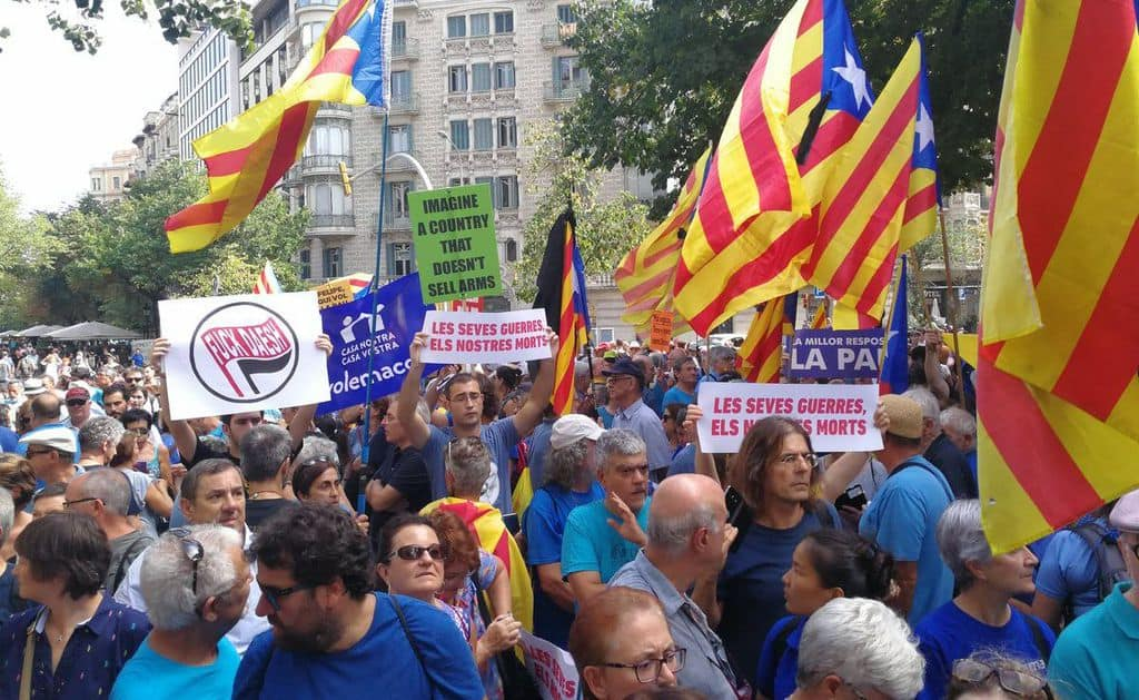 """""""Вашите войни са нашите мъртъвци,"""" пише на два от плакатите сред участниците в шествето из Барселона на 26 август в памет на жертвите на атентатите от 17-18 август и против тероризма. Сред множеството се веят знамената на каталунската независимост. Снимка: Twitter"""