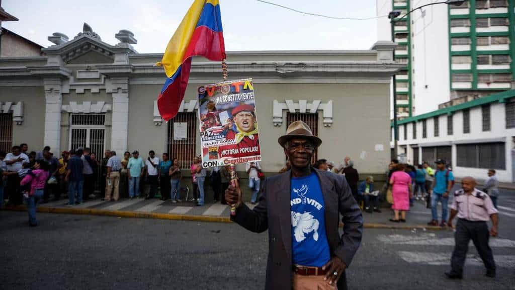 Очакващ реда си гласоподавател позира за снимка на фона на опашката за изборната секция - с венесуелско знаме и саморъчно подготвен плакат с лика на Уго Чавес. Снимка: Resumen Latinoamericano