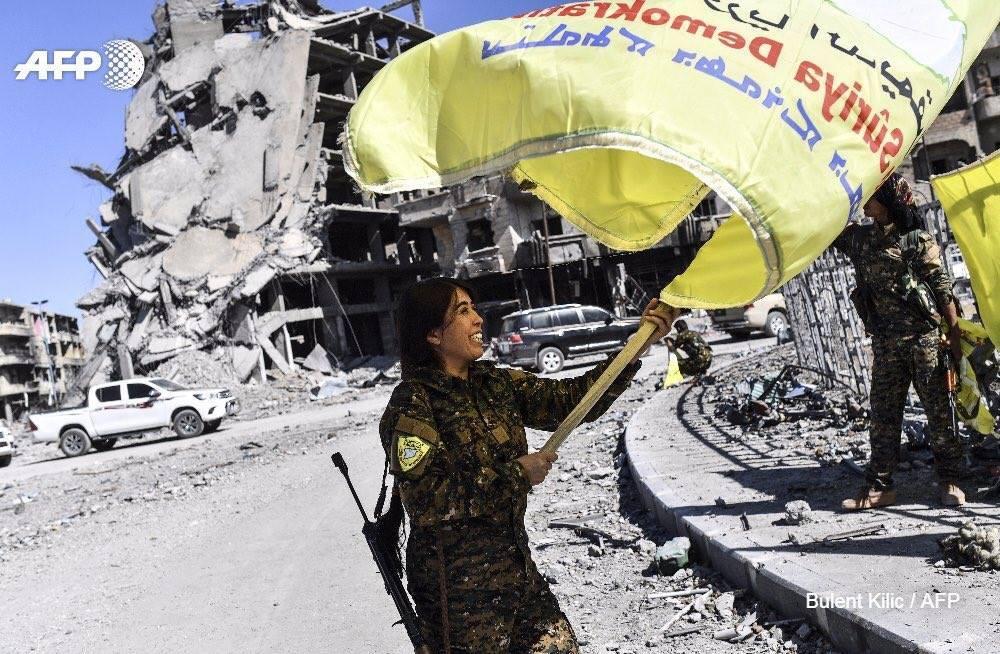 Командирът на операцията в Рака Рожда Фелат развява знамето на Сирийските демократични сили след окончателната победа.