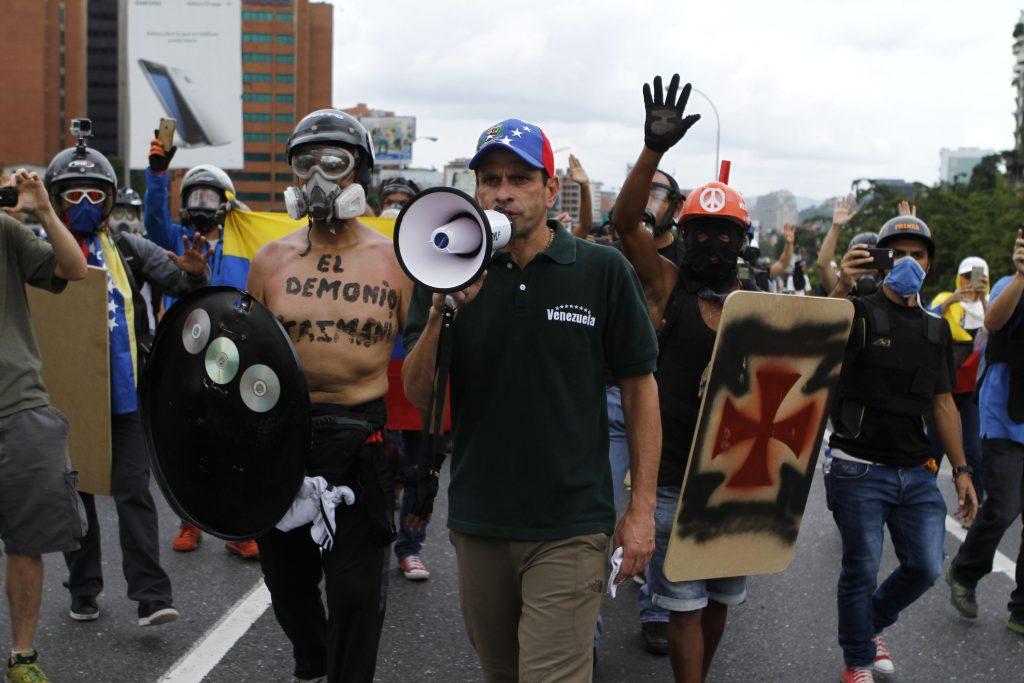 Венесуелският опозиционен водач Енрике Капролес (с мегафона) нахъсва протестиращи по вмене на антиправителствените безредици в Каракас през май т.г. Снимка: Resumen Latinoamericano