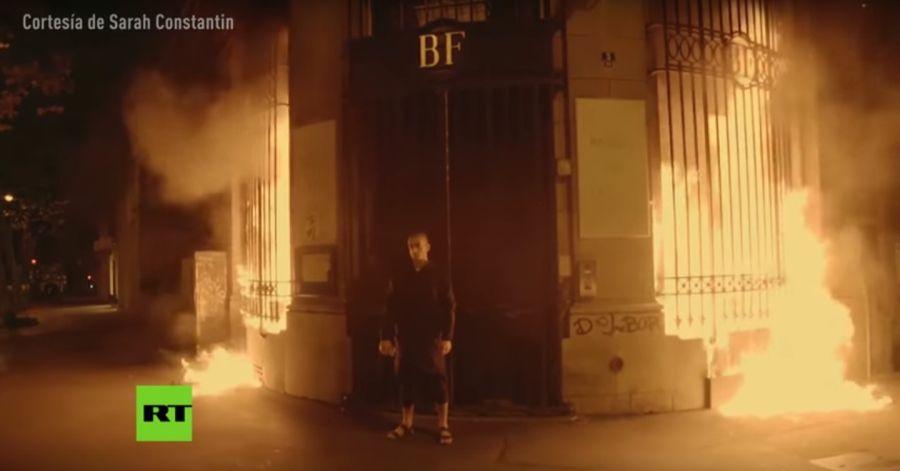 Павленски изчаква да бъде арестуван от полицаите, записвайки своята акция (снимка: YouTube, RT)
