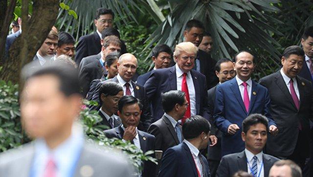 """Путин и Тръмп разговарят """"на крак"""", до тях сияе усмихнат виетнамският президент Чан Дай Куанг, а от другата му страна е китайскиет лидер Си Цзинпин"""