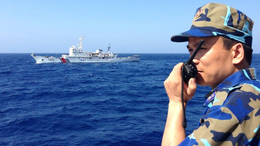 Капитан на виетнамски патрулен кораб докладва на командването си, докато отсреща обикаля и китайски патрулен кораб