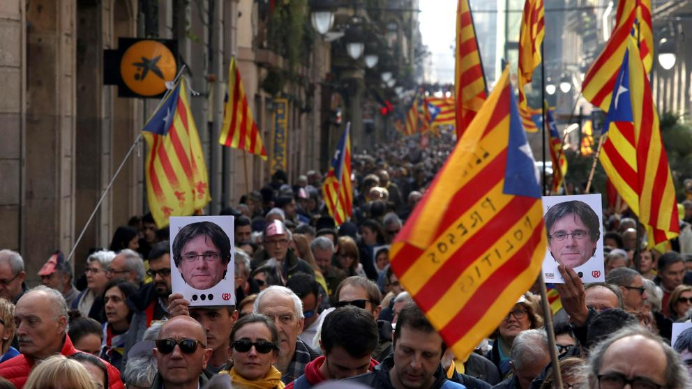 Участници в масовата демонстрация в Барселона срещу отлагането на парламентарната сесия за издигане на премиерската кандидатура на Карлес Пучдемон носят негови портрети. Снимка: La Vanguardia