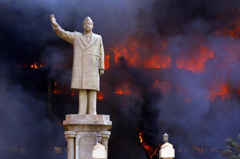 Статуя на Садам Хюсеин пред горящата сграда на Националния олимпийски комитет, Багдад 2003 г. Снимка: The New York Times
