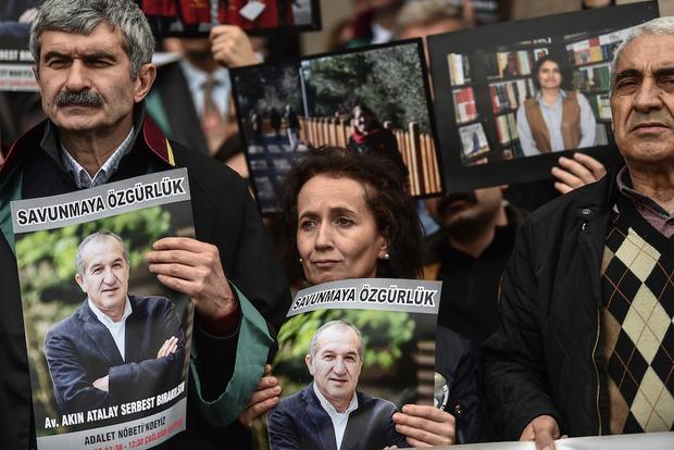 Поддръжници на подсъдимите протестират с техни снимки пред съда, Снимка: AFP