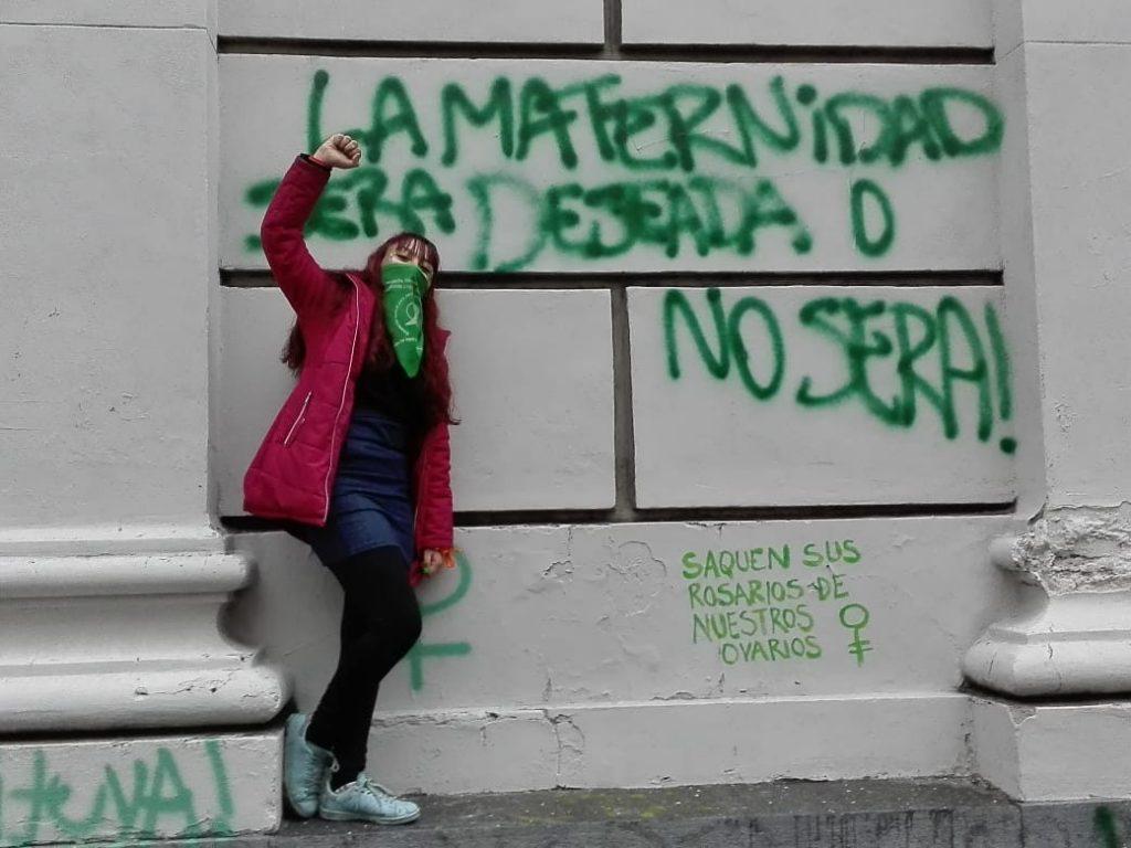 """Привърженичка на легализацията на аборта пред надпис на стена в Буенос Айрес, който гласи: """"Майчинството или трябва да бъде желано, или не трябва да бъде!"""". Отдолу с по-малки букви е добавено: """"Извадете молитвените си броеници от яйчниците ни"""". Снимка: Resumen Latinoamericano"""